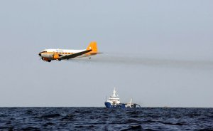 A plane drops chemicals to help disperse oil from a leaking pipeline that resulted from last week's explosion and collapse of the Deepwater Horizon oil rig in the Gulf of Mexico near the coast of Louisiana Tuesday, April 27, 2010. (AP Photo/Patrick Semansky)